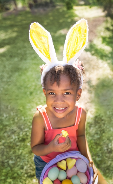 Cute African American girl eating and enjoying Easter candy wear