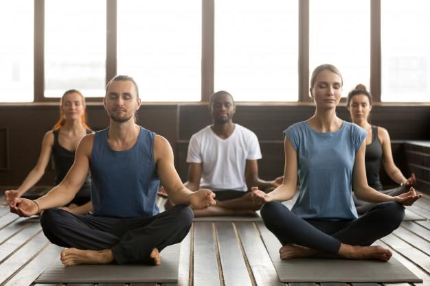 yoga_grupo-jovenes-deportistas-sentados-ejercicio-sukhasana_1163-4940