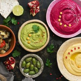 colorful-varied-hummus-caponata-olives-pita-pomegranate-dark-rustic-background-vegetarian-diet-food-top-view-flat-132269735
